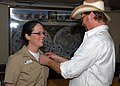 US Navy 081118-N-0515W-157 Ensign Susan Barrett, Combat Weapons Division officer aboard the amphibious assault ship USS Bonhomme Richard (LHD 6), receives her Surface Warfare Officer pin from country music singer and songwriter.jpg