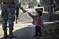US Navy 081206-N-1810F-137 An Iraqi National Policeman gives candy to a child while on a walking patrol through the Rashid community in Bahgdad.jpg