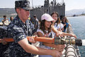 US Navy 100625-N-7638K-200 Quartermaster 3rd Class Michael Bell, from Tampa, Fla., demonstrates the ship's fire hose to students of Maestral Orphanage aboard the Oliver Hazard Perry-class frigate USS Taylor (FFG 50).jpg