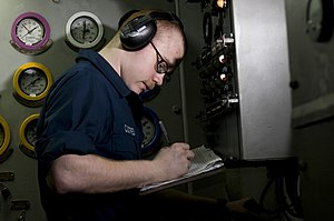 US Navy 120110-N-TZ605-152 Engineman Fireman Damian Custred charts gauge readings in an emergency diesel generator space.jpg