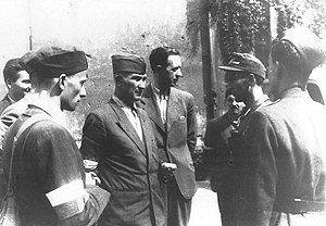"Tadeusz Żenczykowski - General Antoni Chruściel (pseudonym ""Monter"") (center) and officers of the Bureau of Information and Propaganda of the headquarters of Armia Krajowa, in the yard of the main post office in Plac Powstańców Warszawy (then Plac Napoleona) during the Warsaw Uprising. From left to right: Zygmunt Ziółek (pseudonym ""Sawa""), Jan Rzepecki (""Wolski""). obscured by Lech Sadowski (""Wasyl"") in the left foreground, General Chruściel, Żenczykowski and three others to the right."
