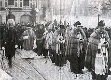 The picture shows an elevator of high church dignitaries accompanied by military or police personnel.  Onlookers and fellow marchers can be seen in the background.