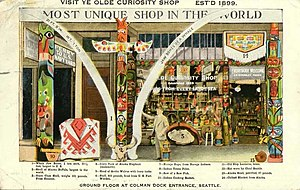 """Ye Olde Curiosity Shop - This 1922 postcard shows Ye Olde Curiosity Shop in its home at that time on Colman Dock. Today, this site is part of Pier 50, the Washington State Ferry Terminal. The postcard shows a variety of artifacts on display in front of the shop, including whale jaw-bones (""""1 ton each, 22½ feet, largest in U.S.""""), a giant clam shell (""""weighs 161 pounds, from Equator""""), a hat worn by Chief Seattle, and several totem poles."""