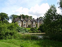 Country house, partially obscured by greenery, viewed from across a pond. The observable frontage comprises five gables, with a turret between the four gables on the left and the rightmost gable.