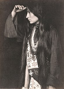Photo of Zitkála Šá in profile, wearing Native American dress, with long dark hair hanging below waist, holding hand at forehead and looking into the distance