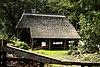 foto van Boerderij, houten kapschuur. Terzijde van de boerderij staat een open houten kapschuur, riet gedekt en met een sporenkap ter lengte van vier vakken. Het derde gebint heeft naast de beide korbelen een tweetal gordingschoren