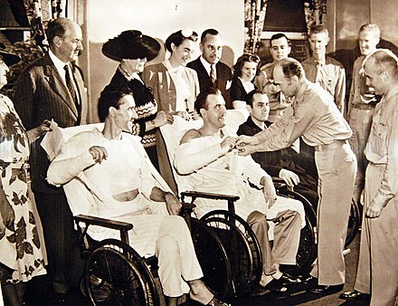 An injured pilot received the Distinguished Flying Cross at Walter Reed Hospital from Maj. Gen. Millard F. Harmon in 1942. 111-SC-21321AC (34281999011).jpg