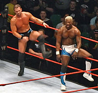 Two men, one Caucasian and one African American, are beside each other and both about to exit a wrestling ring with red ropes. The Caucasian male has light brown hair, and is wearing black wrestling tights, with black wrestling boots and black kneepads. The African American wrestler has dyed blond hair, and is wearing white and blue wrestling tights, and matching wrestling boots with black kneepads. The audience is visible in the background of the photo.