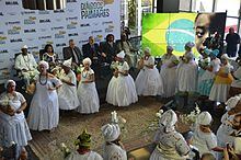 Women in white dresses in a semi-circle
