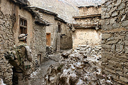 A corpsman in desert fatigues stands in the middle of a group of very old houses.