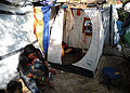 A Haitian barber charges a wind-up radio outside a temporary shelter he is using as a barbershop in Petionville, Haiti 100222-N-HX866-008.jpg