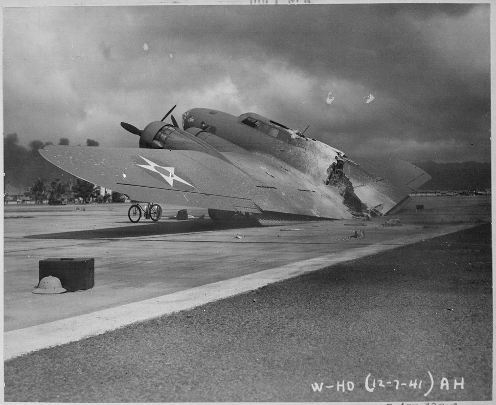 A burned B-17C aircraft rests near Hangar Number Five, Hickam Field, following the attack by Japanese aircraft. Pearl... - NARA - 520602