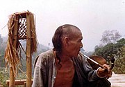 An Akha man smokes a pipe. Although this pipe was described as an opium pipe by the photographer, a true opium pipe requires an external heat source. Still, opium can be smoked by mixing it with tobacco, as in madak and ack ack.