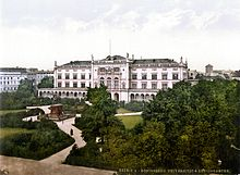 Photographie en couleurs datant (entre 1890 et 1905) de l'université Albertina de Kœnigsberg, où étudia Hoffmann. Derrière un bosquet d'arbres et un jardin se découpe la façade blanche du bâtiment principal.