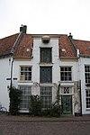 Gepleisterd woonhuis met rechte kroonlijst, in midden verhoogd met hijsbalk