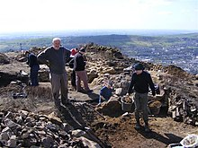 A group of archaeologists digging, with rubble in the foreground.