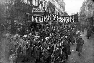 Russian Revolution - Armed soldiers carry a banner reading Communism, Nikolskaya Street, Moscow