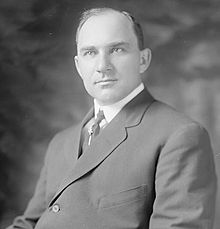 A man with receding black hair wearing a black jacket and tie and white shirt