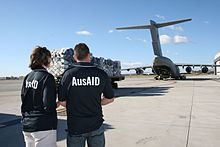 "Colour photo of a woman and a man wearing blue polo shirts with ""AusAID"" on the back looking at a large military transport aircraft at an airport. A trailer loaded with supplies is in front of the two people."