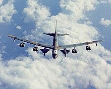 Vista aérea del B-52 vuela por encima de las nubes blancas y el mar.  Lleva dos vehículos de forma triangular debajo de las alas entre el fuselaje y los motores internos.