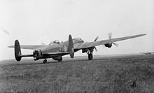 Rear three-quarter view of four-engined military aircraft with twin tailfins, parked on landing ground