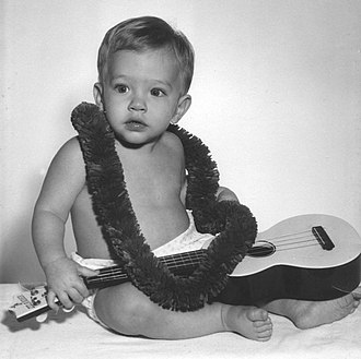 "Ukulele - Boy in Hawaii wearing lei and holding a Maccaferri ""Islander"" plastic ukulele"