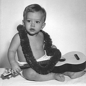 """Ukulele - Boy in Hawaii wearing lei and holding a Maccaferri """"Islander"""" plastic ukulele"""