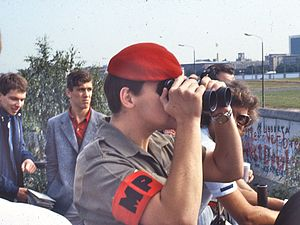 Red beret - Red Beret-wearing, British, Royal Military Police member uses field glasses to look across the Berlin Wall from a viewing platform on the western side, 1984.