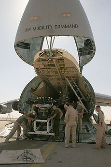 color photo of Marines pushing carted equipment from the open bay of a large cargo jet