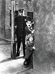 A black and white image of a young man with a mustache and a bowler hat peaking around from behind a brick corner with a police officer behind them