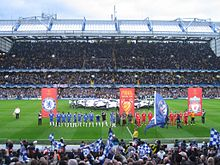 The Chelsea (blue) and Liverpool (red) teams line up side-by-side in front of banners bearing their club crests and the Champions League final logo. In the background, a flag bearing the Champions League logo is waved over the centre circle, while the main stand is further back, full of spectators. In the foreground, Chelsea fans wave blue flags bearing their club crest.