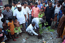 Community leader helps plant a lemon tree using used toilet bag as fertilizer (3683082357).jpg