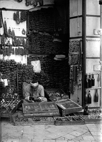 Hebron glass - The jewellery store shows evil eye beads and Hebron-made glass bracelets sold alongside the shopkeeper's main ware of silver or metal wire. Photo taken 1900-1920 by American Colony, Jerusalem.