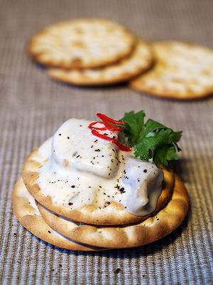Crackers with herring and garlic sauce.