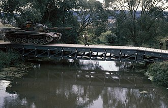 Medium Girder Bridge - An M60A3 main battle tank crosses a medium girder bridge during Exercise REFORGER '83 in Germany, 1983