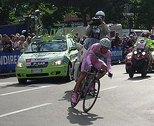 A cyclist on his bicycle, wearing a skintight pink jersey with pink shorts and shoes. A lime green car and two motorcycles follow behind him, and spectators are visible on the roadside behind barricades.