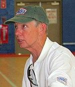 Um homem caucasiano mais velho usando um boné verde sujo e camisa pólo branca está sentado em uma cadeira no meio de uma quadra de basquete.  Ele está olhando para a esquerda, enquanto conversava com uma pessoa fora da câmera.