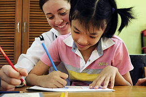 Defense.gov News Photo 110302-N-9094S-060 - U.S. Navy Seaman Krista Stelzner draws pictures with a child during a community service event at the Bukit Harapan Therapeutic Community Center in.jpg