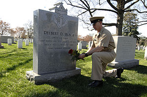 Delbert Black - The twelfth Master Chief Petty Officer of the Navy (MCPON) Rick D. West lays a single red rose at the gravesite of the first MCPON Delbert Black at Arlington National Cemetery.