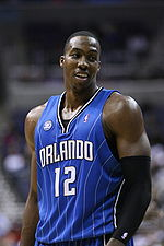 "A man, wearing a blue jersey with a word ""ORLANDO"" and the number ""12"" written in the front, is standing in front of the crowd."