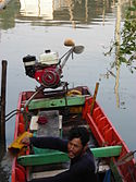 Fisherman empties his boat with a bucket.jpg