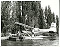 Fishing - Trout Publicity Caption Fishing guide returns a satisfied client holding a rainbow trout, to her chartered float plane, Lake Taupo.jpg