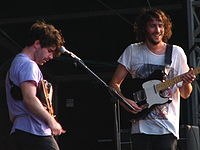 Two guitarists are performing a song live on a stage, in front of a mic mounted on a microphone stand.