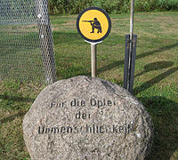 "Boulder carved with the words ""Für die Opfer der Unmenschlichkeit"". In the background are a section of border fence and a yellow sign showing a kneeling soldier taking aim with a rifle."