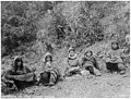 Group of indigenous people sitting on shrub-covered hillside, Yukon Territory, between 1904 and 1908 (AL+CA 7970).jpg