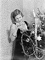 Hans steekt de kaarsjes aan in de versierde kerstboom, Bestanddeelnr 189-1126.jpg