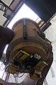 Uma vista ao longo do tubo do telescópio.  No fundo, a fenda de observação aberta na cúpula mostra um céu superexposto.  No primeiro plano, alguns dispositivos eletrônicos são montados na extremidade inferior do tubo do telescópio, com cabos bagunçados.  Existem duas caixas laranja, dois racks amarelos de algum tipo e alguns outros dispositivos.  Na lateral do tubo do telescópio, diretamente na frente da câmera, há um cilindro preto estreito;  à sua direita, um conjunto de placas de peso é aparafusado ao tubo do telescópio.