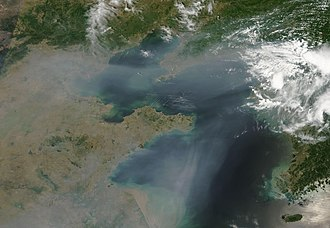 Pollution in China - North-Eastern China from space, 2009. Thick haze blown off the Eastern coast of China, over Bo Hai Bay and the Yellow Sea. The haze might result from urban and industrial pollution.