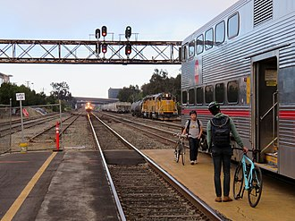 South San Francisco station (Caltrain) - A southbound train holds outside the station while passengers board a northbound train
