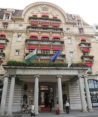 Lausanne Palace - The main entrance, with flags of Switzerland, Vaud, the Leading Hotels of the World and the Olympic flag (2013).
